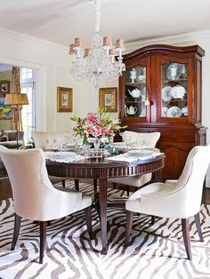 How to Modernize Your Dining Room - Update a traditional matching set by replacing the seating with curvy tufted chairs upholstered in a pale fabric to contrast with the dark rich wood – a zebra motif rug also adds a modern edge.