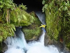 Foto: PIC BY STEPHEN ALVAREZ / NATIONAL GEOGRAPHIC STOCK / CATERS NEWS - (PICTURED:A caver makes his way into the cave behind Ora Waterfall, New Britain Island, Papua New Guinea) - These are the fascinating images which show dare-devil climbers descending hundreds of feet below the earths surface. Plunging down the largest of waterfalls, shimmying through the tightest of underground spaces and swimming in the worlds most remote underground rivers -