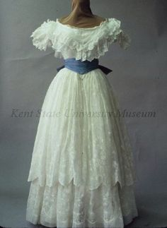 Dress Date1855-1860 CultureAmerican, attributed DescriptionWhite embroidered cotton. Bodice: wide neck, dropped puffed sleeves, ruffled as neck. Skirt: 2 tiers with scalloped edge, embroidered all over in white cotton as flowers and vines.