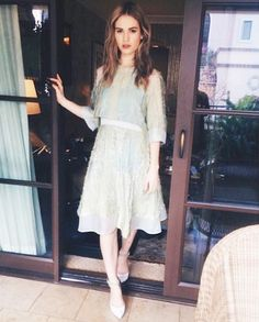 Actress Lily James wears a sheer, feminine dress with white ankle-strap heels