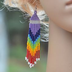 Long dangling fashionable seed bead earrings. Native American style beadwork. Handcrafted long fringe rainbow earrings. Beautiful work of colors. Happy Beads! Size 11 seed bead earrings; purple, blue, green, yellow, orange, white and red beads. Approximate earring length 3 1/4 including hypoallergenic hook. 5/8 wide.  Made with love one piece at a time.  Here are more seed bead earrings you may like http://www.etsy.com/shop/VickiBeadsandLeather?ref=hdr_shop_menu§ion_id=17155949  Thanks for…