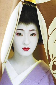Kimina, a geiko of Miyagawa-cho, looks out through the noren (curtain) of a restaurant across the street from her okiya