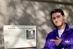 Milton Zerman posa junto a la placa conmemorativa de Robert Merriman (comandante del Batallón Abraham Lincoln) colocada en la fachada del antiguo hogar de los Merriman en Berkeley.