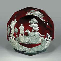 Antique Baccarat sulphide footed paperweight, with a landscape scene of a hunter and his dog in a tree-lined field, on translucent ruby ground