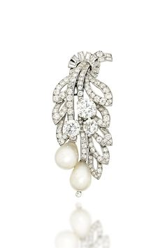 AN ART DECO NATURAL PEARL AND DIAMOND CLIP BROOCH, BY CARTIER -  Modelled as a foliate spray, the old-cut diamond openwork leaves, to similarly-set flowerheads and natural pearl drop shaped buds, measuring approximately 9.7 x 12 and 9.0 x 12.1mm respectively, with baguette-cut diamond tied ribbon surmount, circa 1935.