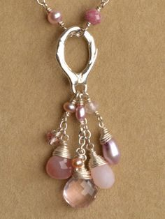 "Rose Quartz, Pink Opal, Agate, Pink Cultured Pearl and Pink Topaz.The wire wrapped stones suspend from delicate chain in different lengths giving ""Love Divine"" essence of depth.  This pendent would be fabulous on a charm necklace or a simple cord to change the look, and the oval ring on top allows for the piece to fit over a variety of options.  Sterling silver or gold vermeil, and measures approx. 2.75"" from the top of the charm ring."