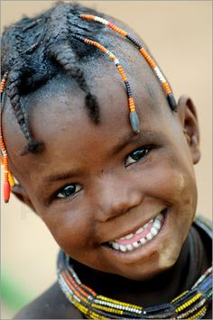 Africa | Portrait of smiling young Himba girl with braided hair. Opuwo. Namibia. BelAfrique - Your Personal Travel Planner - www.belafrique.com