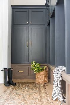 A vintage gold and blue rug sits in front of a brown oak mudroom bench fitted beneath black open lockers located under black shaker cabinets donning b… – Mudroom Entryway Mudroom Cabinets, Mudroom Laundry Room, Mudroom Cubbies, Mud Room Lockers, Mudroom Benches, Bathroom Cabinets, Shaker Cabinets, Dark Cabinets, Custom Home Builders