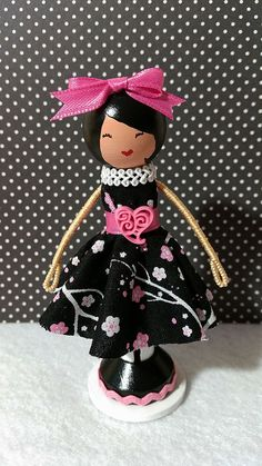Amelia, a super cute wooden clothespin doll stands just over four inches tall, and is uniquely hand painted in vibrant colors and wears a real cotton fabric dress in a pink black and white floral print.
