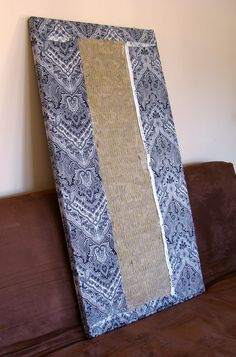 Ugly picture, but click through for an article on DIY acoustical panels. All you need is a bit of fiberglass. You can wrap it in any sound-transparent fabric—silkscreened burlap could be really cool.
