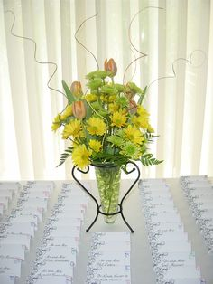 Simple arrangement of Spring flowers for a yellow, green, and orange wedding. Designed by Whimsical Welcomes.