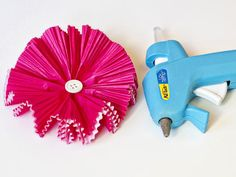 How to Make Paper Flowers Using Cupcake Liners: Turn the flower over and glue a button, jewel or small pom to the center of the flower. From DIYnetwork.com