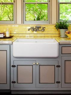 A sunny-yellow backsplash pairs perfectly with soft blue cabinetry in this cheery kitchen. Featured on both the countertops and the backsplash, the traditional shape of the subway tiles creates undeniable vintage character. The buttery-yellow hue of the t Vintage Farmhouse Sink, Vintage Kitchen, Farmhouse Sinks, Farmhouse Trim, Farmhouse Interior, Interior Modern, Kitchen Colors, Kitchen Decor, Kitchen Yellow