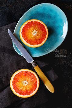 Bloody Orange - Slised Sicilian Blood orange fruit on bright turquoise ceramic plates over black background, with vintage knife and textile napkin. Flat lay