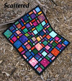 Scattered quilt pattern redesigned as a miniature quilt in batiks