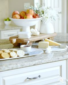Fall centerpiece of a bowl of apples on the kitchen island for fall decor with a cheese board for guest apps.