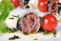 Appetizer of salami with mozzarella, olives, cherry tomatoes on skewers with basil oil