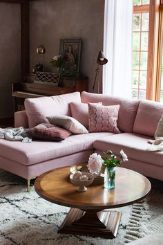 A pale pink sofa adds modern country charm to plaster walls and wood accents in this sweet living room. Photo by Heidi's Bridge.