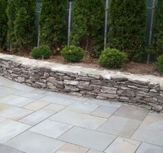 bluestone patio with natural stone wall. We have this exact wall so this is what the new patio could look like