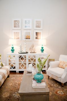 Light and bright living room with white upholstery, floral rug, turquoise accents