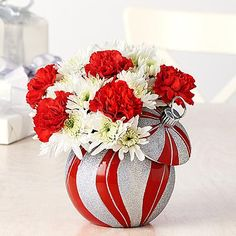 Bundled with Joy Ornament - This fun red and silver ornament is filled with delightful white cushion poms and red carnations. Adds seasonal flair to any home décor.