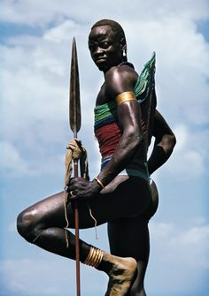 Like a Nile crane, a Dinka warrior stands guard on one foot.  His corset will stay in place day and night, only being changed for one of a different colour when he progresses on to the next age set |  © Angela Fisher, from her fabulous book, Africa Adorned.