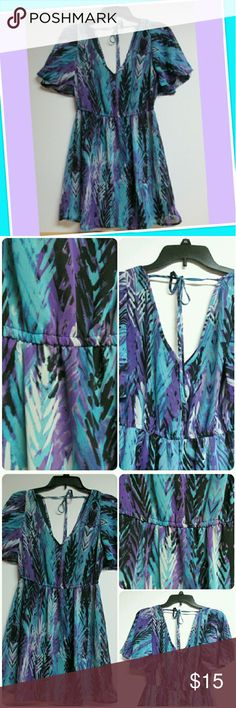 """Fab Fun & Feathers Fabulous little dress with abstract feather print in vivid shades of turquoise, purples,black and light grey. Has deep v-neck front and back w/ tie across   the shoulders. Lovely fluttery sleeve. Fully lined except sleeves. Size 5 by Johnny Martin.  Elastic waist, skirt approx. 18"""" long from waist. Excellent Condition.  Proceeds go to charity. Johnny Martin Dresses"""
