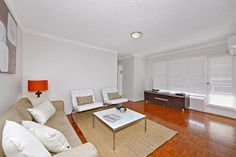 Contemporary Lounge Room with orange highlights. #propertystylng #instantinteriors