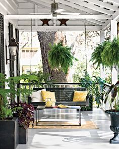 The porch is decked out with a mix of classic and contemporary touches, including a dark-painted slatted swing, a concrete-and-steel coffee table, zinc planters, and sunny yellow pillows.