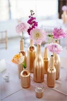 7 Clever DIY Centerpieces You Should Copy Right Now: Flowers styled in gold painted bottles. So chic for an adult birthday dinner party.