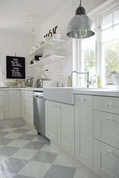 Swoon. Gorgeous Swedish kitchen with white cabinets, open shelving, farmhouse sink (IKEA?), industrial style pendant, and gray checkerboard painted wood floors.