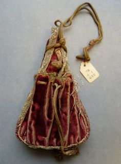Full: Front   Description  Purse; crimson velvet; in the shape of a powder flask, with stiffened centre padded with horsehair; a drawstring pouch on each side and silver braid round edge. Date      16thC (?)  Materials      silver term details     silk term details  Technique      braided term details     velvet  Dimensions      Length: 4.75 inches