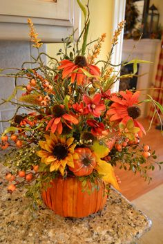 This arrangement is full of fall flowers, berries, pumpkins and greenery and is made in a pumpkin shaped basket. It would be perfect mixed in with your fall decor or used as a centerpiece. Pumpkin Arrangements, Fall Floral Arrangements, Pumpkin Centerpieces, Centerpiece Ideas, Halloween Flower Arrangements, Table Centerpieces, Fruits Decoration, Pumpkin Decorations, Flower Decoration