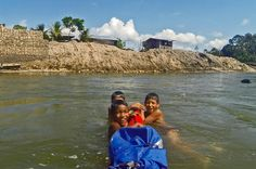 Des enfants s'agrippent au kayak de Tarran Kent-Hume au Pérou.