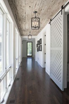 Check out this rustic hallway! Dark wood floors with the reclaimed wood ceiling. The white sliding barn door adds a dramatic effect. The cage pendant lights down this hallway gives it a dramatic and gorgeous look! Add some rustic elegance to your home! Deco Design, Design Case, Book Design, Design Design, Style At Home, Barn Door Designs, House Ideas, Dark Wood Floors, Reclaimed Wood Floors