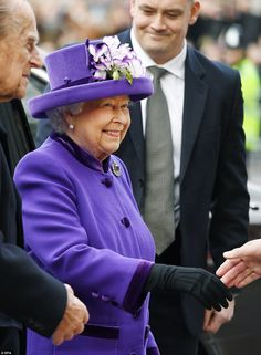 The Queen was wearing a purple crepe coat and matching hat by Angela Kelly with an amethys...