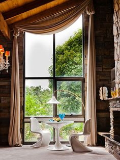 12 Ways to Use Panton Chairs: The Panton chairs, pedestal table, and arc lamp make an interesting tableau among the stacked stone fireplace, crystal chandeliers, and floor-length drapery.
