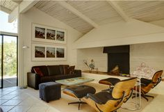 Architect Cliff May's classic mid-century style Alisal Ranch Home: Dining room with fireplace, exposed wooden beams, Eames furniture