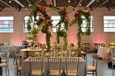 A custom built geometric structure dripping with floral. The table scape is filled with gorgeous candle votives and thoughtful details.