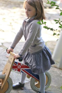 Fillette à vélo. Cardigan à noeud et jupon plumetis. Girl on a bike Knot cardigan and skirt.