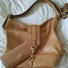 Coach Authentic  purse with wallet This beautiful tan leather shoulder bag has three large storage compartments. It does have a water stain that is hidden under the clasp belt, but otherwise in great condition. It comes with a gorgeous matching Coach wallet and protective bag.  Come get it!  You deserve it! Coach Bags Shoulder Bags