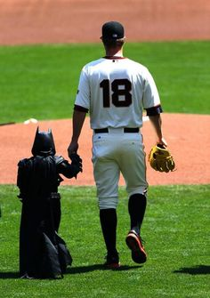 "4/8/14. Is this frickin' adorable or what?  It's the Home Opener for the SF Giants and Matt Cain walks ""Batkid"" (Miles Scott) to the mound so he can throw out the ceremonial first pitch."