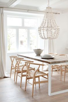 chandelier in neutral dining room with wood chairs