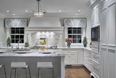 White kitchen makes extensive use of white marble on the countertops and large backsplash over hooded range, contrasting with darker natural hardwood flooring.