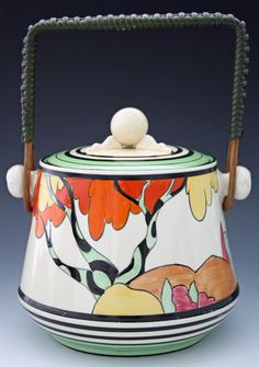 Biscuit Barrel -- A beautiful and rare Clarice Cliff biscuit barrel which has been hand painted in the very desirable and highly collectable Honolulu pattern. The pattern depicts stylised trees with orange and yellow foliage. This biscuit barrel comes with it's original wicker handle.