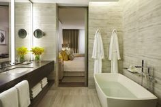 Bathrooms in soothing grays with accent colors of Wedgewood blue and butter cream yellow ... and a TV in the bathroom mirror!  @Mandy Bryant Dewey Seasons Hotel Toronto.