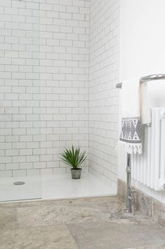 The silver and grey tones of our Silver Tumbled Travertine really compliment the stylish white metro tiles of the shower enclosure. #bathroomgrey