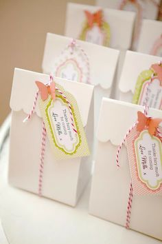 Beautifully decorated party favour bags are also easily made. It's all in the papers used in the tags and the style of font used. They have just added some little scrapbook butterfly cut outs and some butchers string. X