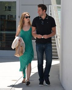 Happy: Emily held onto John's arm as they strolled to the movie theatre