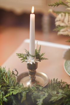Easy wintry wedding decorations - white candles, fir sprigs, berries and pretty white blooms